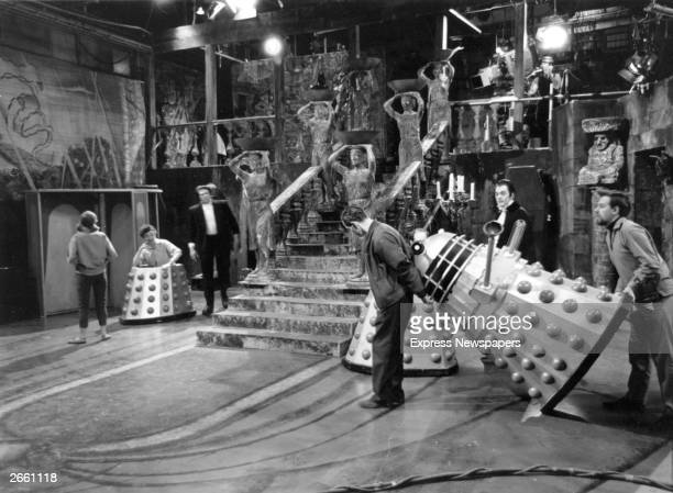 Stage hands seen carrying 'Daleks' on the set of the television programme 'Dr Who Meets Frankenstein'
