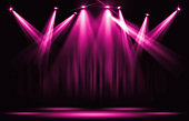 Stage lights. Pink violet spotlight with certain through the darkness.