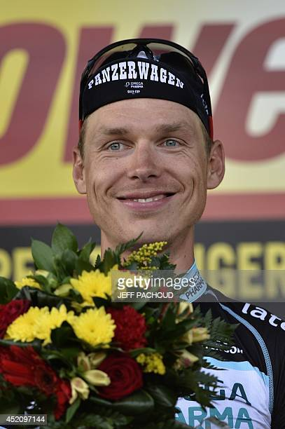 Stage winner Germany's Tony Martin celebrates on the podium after winning the 170 km ninth stage of the 101st edition of the Tour de France cycling...