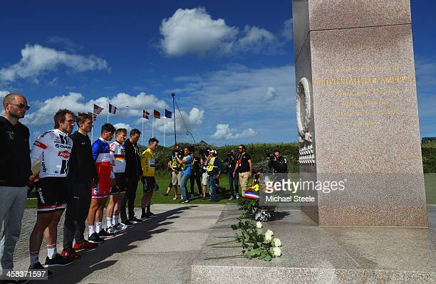 Stage winner Mark Cavendish of Great Britain and Team Dimension Data and fellow riders observe a minutes silence at a war memorial at Utah Beach...