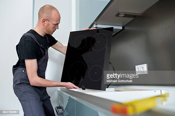 A staged photo of a workman installing a fitted induction hob in a kitchen on October 25 2013 in Berlin Germany