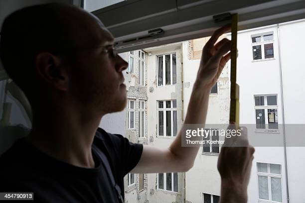 A staged photo of a workman measuring up for a new window frame on October 25 2013 in Berlin Germany