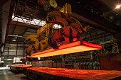 Im Stahlwerk wird eine glühende Stahlbramme verladen