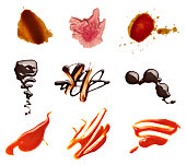 collection of various coffee, wine, ketchup and chocolate stains on white background. each one is shot separately