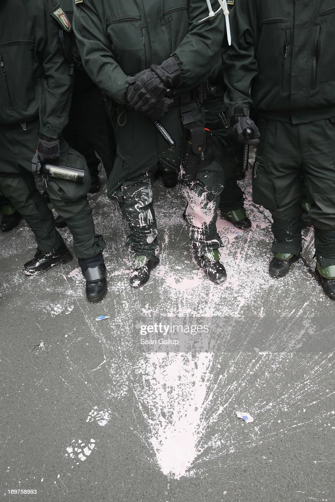 A stain left by a paint packet thrown by a demonstrator lies at the feet of riot police during the main Blockupy demonstration in the financial district on June 1, 2013 in Frankfurt am Main, Germany. Thousands of protesters are marching to demonstrate against capitalism, European Central Bank debt policy and the exploitation of textile workers in Third World countries, among other issues.