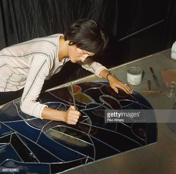 A stained glass artist bends over a panel and adds final touches France ca 1960s