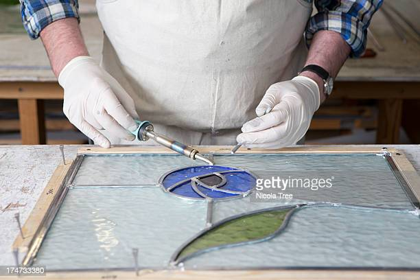 Stained glass maker welding lead on piece