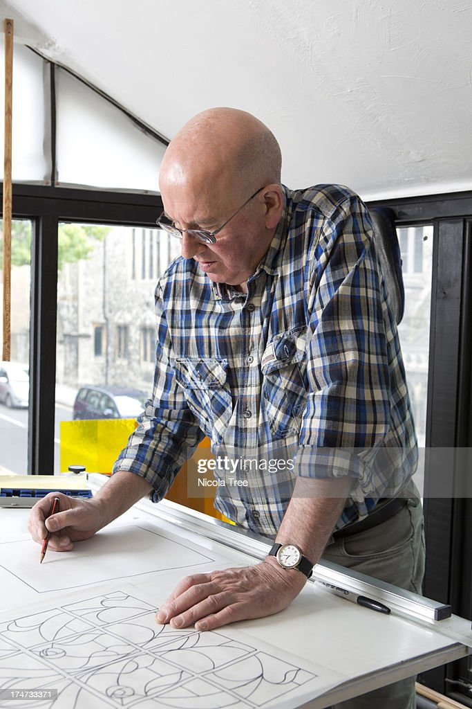 Stained glass maker working on a design : Stock Photo