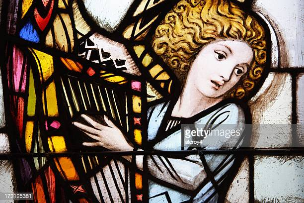 Stained glass window of angel playing the harp
