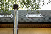 Stainless steel chimney flue  on the tile covered roof with rooftop windows at country cottage .