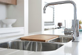 Modern stainless steel faucet and sink on kitchen,with chopping board on top of sink