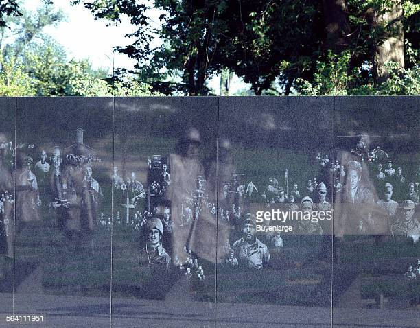 Stainlesssteel troopers on patrol reflect in a wall on which etchings of support personnel taken from actual photos appear at the Korean War Veterans...