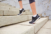Feet of woman wearing sports shoes and walking up stairs on tiptoes