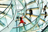 Motion blur of people on a contemporary spiral staircase.