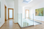 Stairs, glass banister and doors in modern hallway on the attic