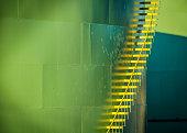 Metal yellow stairs climb a green industrial oil storage tank in Sandwich, Massachusetts