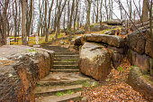 Stairs up among stone granite boulders in the park with trees without leaves. Autumn melancholic landscape on the background gray rainy sky