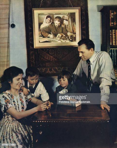 Stalin Personality Cult photograph published on 'Union Soviétique Mai 1953' A typical Soviet family portrayed in their cozy apartment living room in...