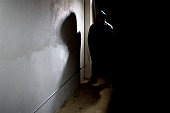 Photo of a hooded criminal stalking in the shadows of a dark street alley.  The hooded man is a silhouette and hiding in the dark.  The man is a criminal waiting to ambush victims.  The concrete walls