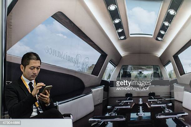 A stall attendant uses his mobile phone in front of a poster of the interior of a hearse vehicle at the AFE 2015 Asia Funeral and Cemetery Expo and...