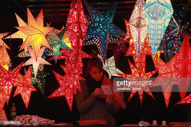 A stall holder arranges her display of Christmas stars at Munich Marienplatz Christmas market on December 9 2011 in Munich Germany The Marienplatz...