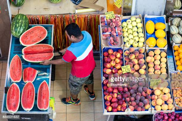 A stall holder cuts a watermelon at a fruit and vegetable stall inside an indoor market in Rome Italy on Thursday Aug 17 2017 Italy's economic...
