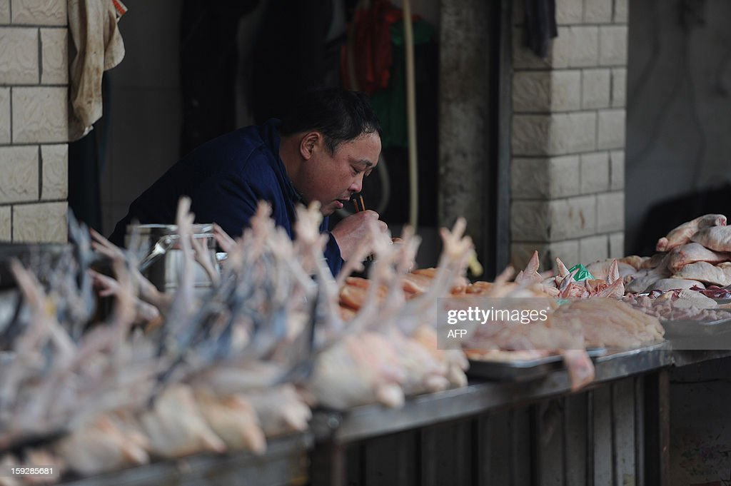 A stall holder eats a meal as he waits for customers in a market in Hefei, central China's Anhui province on January 11, 2013. China's inflation rate slowed sharply in 2012, official data showed on January 11, but analysts warned of increasing price risks this year that may limit scope for measures to boost economic growth. CHINA