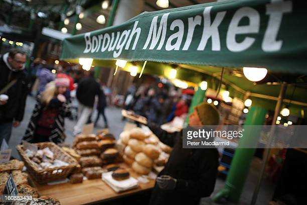A stall holder offers a free sample to customers at Borough Market on February 7 2013 in London England Borough Market London's oldest since 1756 has...