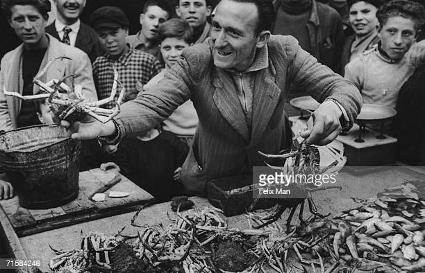A stall holder selling live crabs at a market in an Italian fishing town circa 1950