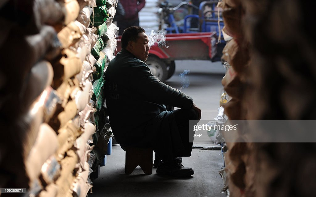 A stall holder smokes as he waits for customers in a market in Hefei, central China's Anhui province on January 11, 2013. China's inflation rate slowed sharply in 2012, official data showed on January 11, but analysts warned of increasing price risks this year that may limit scope for measures to boost economic growth. CHINA