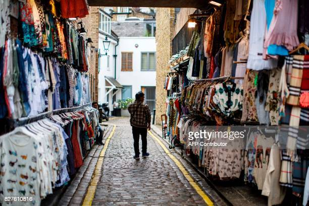 A stall holder walks past his merchandise at Portobello Road Market in the Notting Hill district of west London on August 8 2017 Last week The Bank...