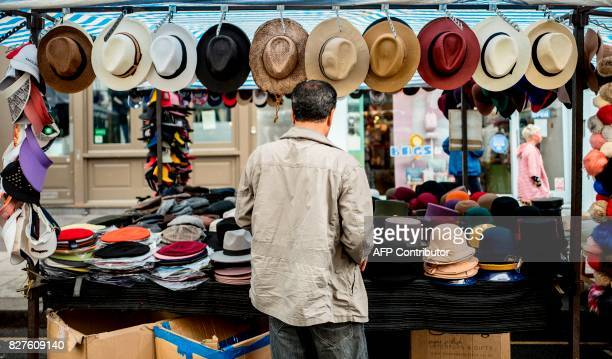 A stall owner prepares merchandise on a stall at Portobello Road Market in the Notting Hill district of west London on August 8 2017 Last week The...