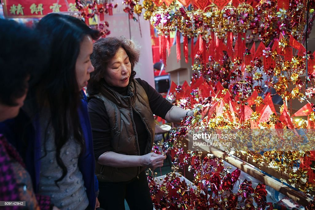 A stall owner (R) shows customers (L) toy windmills, used to bring good fortune, at the Che Kung Temple in the Sha Tin district of Hong Kong on February 9, 2016. The Lunar New Year of the Monkey began on February 8. AFP PHOTO / ISAAC LAWRENCE / AFP / Isaac Lawrence