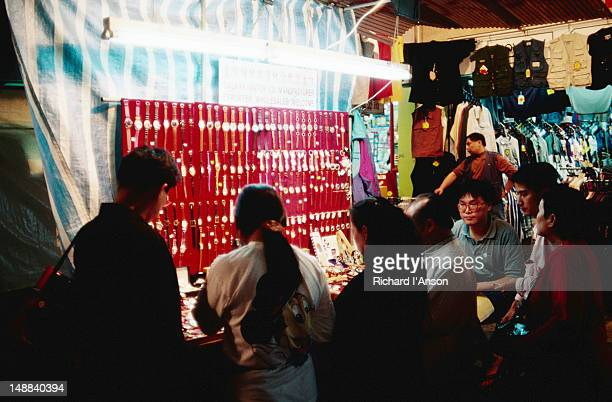 A stall selling watches beneath a single fluorescent tube at the Temple Street night market