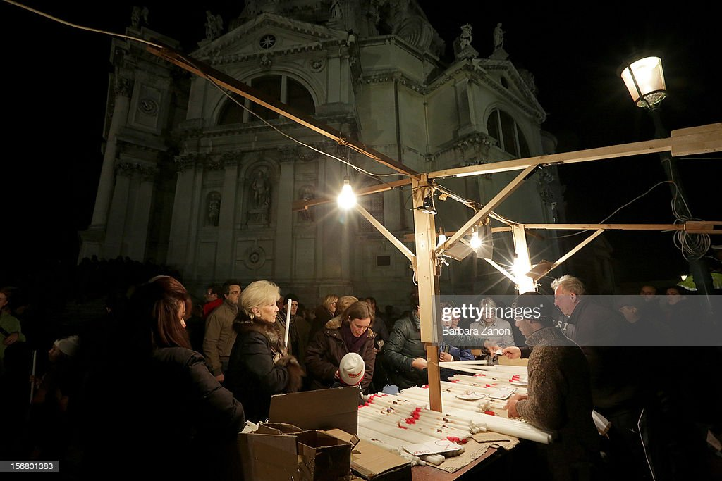 A stall sells candles to venetians outside the Santa Maria Della Salute Church during the Santa Maria Della Salute celebrations on November 21, 2012 in Venice, Italy. During the annual Santa Maria Della Salute celebrations, Venetians make pilgrimage to the Church to give thanks to the Virgin Mary (Maria), who is believed to have brought an end to the plague which struck the city in 1629.