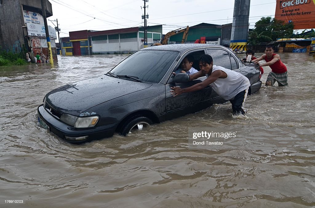 A stalled car is pushed by residents after floodwaters inundated parts of Las Pinas on August 19, 2013 in Las Pinas City south of Manila, Philippines. Tropical storm Trami which was enhanced by monsoon rains swept overnight through the southern metropolitan cities of Manila and leaving huge parts of four provinces underwater forcing residents to evacuate their homes and seek shelter in evacuation centers. At least three fatalities were recorded with thousands more still needing to be rescued.