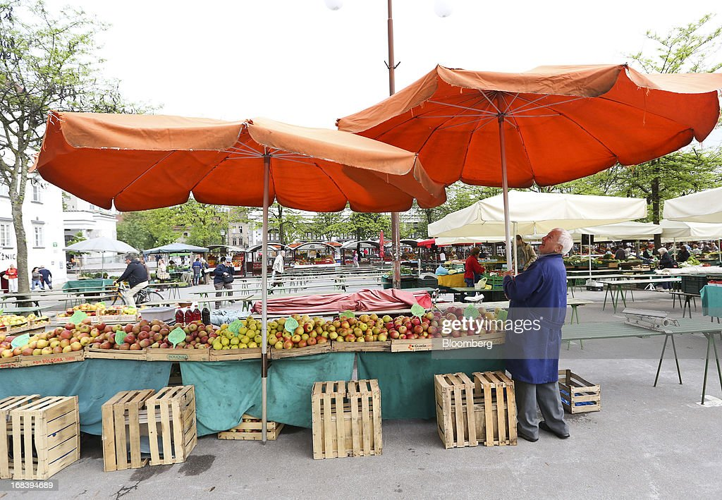 A stallholder arranges a parasol above his display of fresh fruit at an open market in Ljubljana, Slovenia, on Wednesday, May 8, 2013. Slovenia's recession will stretch into next year on weak domestic demand as the euro-area country teeters on the brink of needing an international bailout, the European Commission said. Photographer: Chris Ratcliffe/Bloomberg via Getty Images