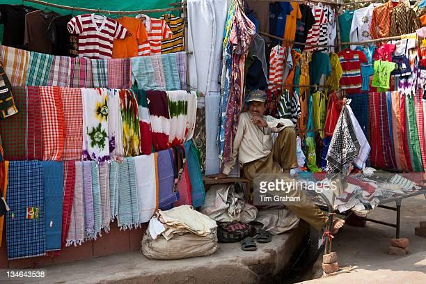 Stallholder selling clothes and sari fabrics and other textiles at Varanasi Northern India