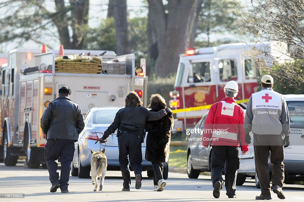 A Stamford Connecticut police officer left walking dog comforts the nextdoor neighbor of the house where an earlymorning fire on December 25 killed...