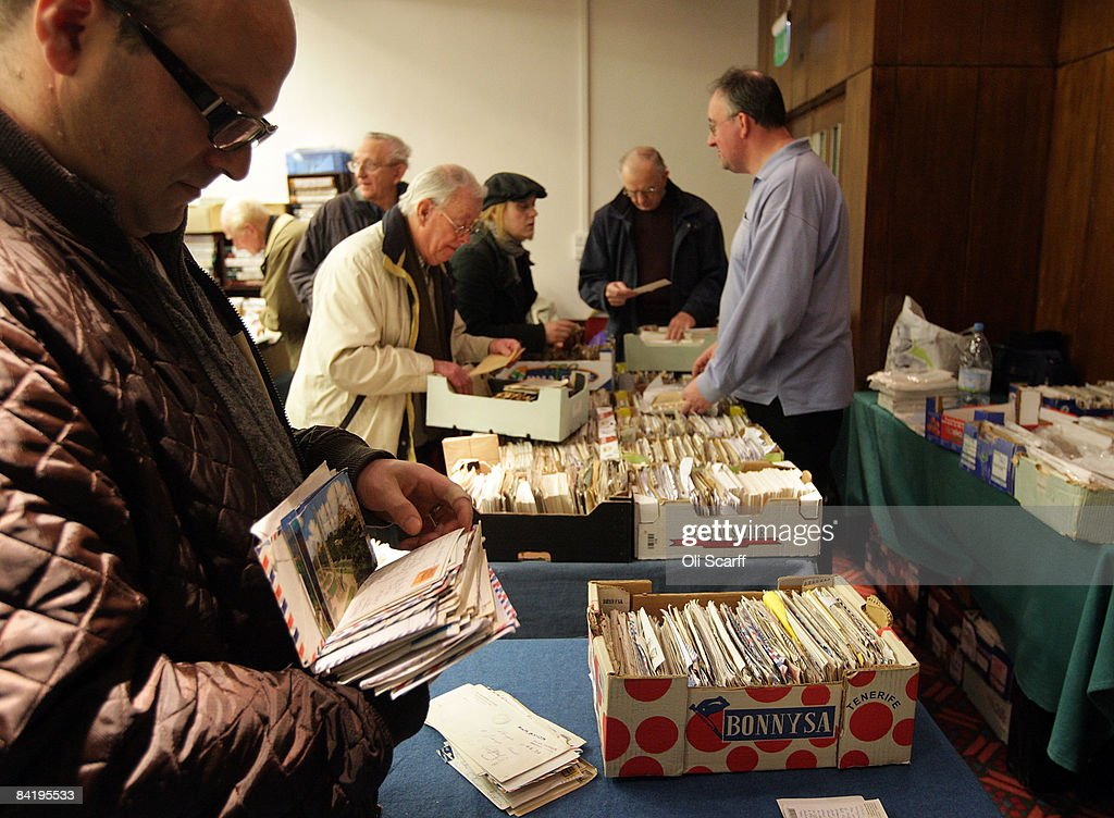 stamp collectors look through boxes of stamps and letters for sale at the strand stamp show