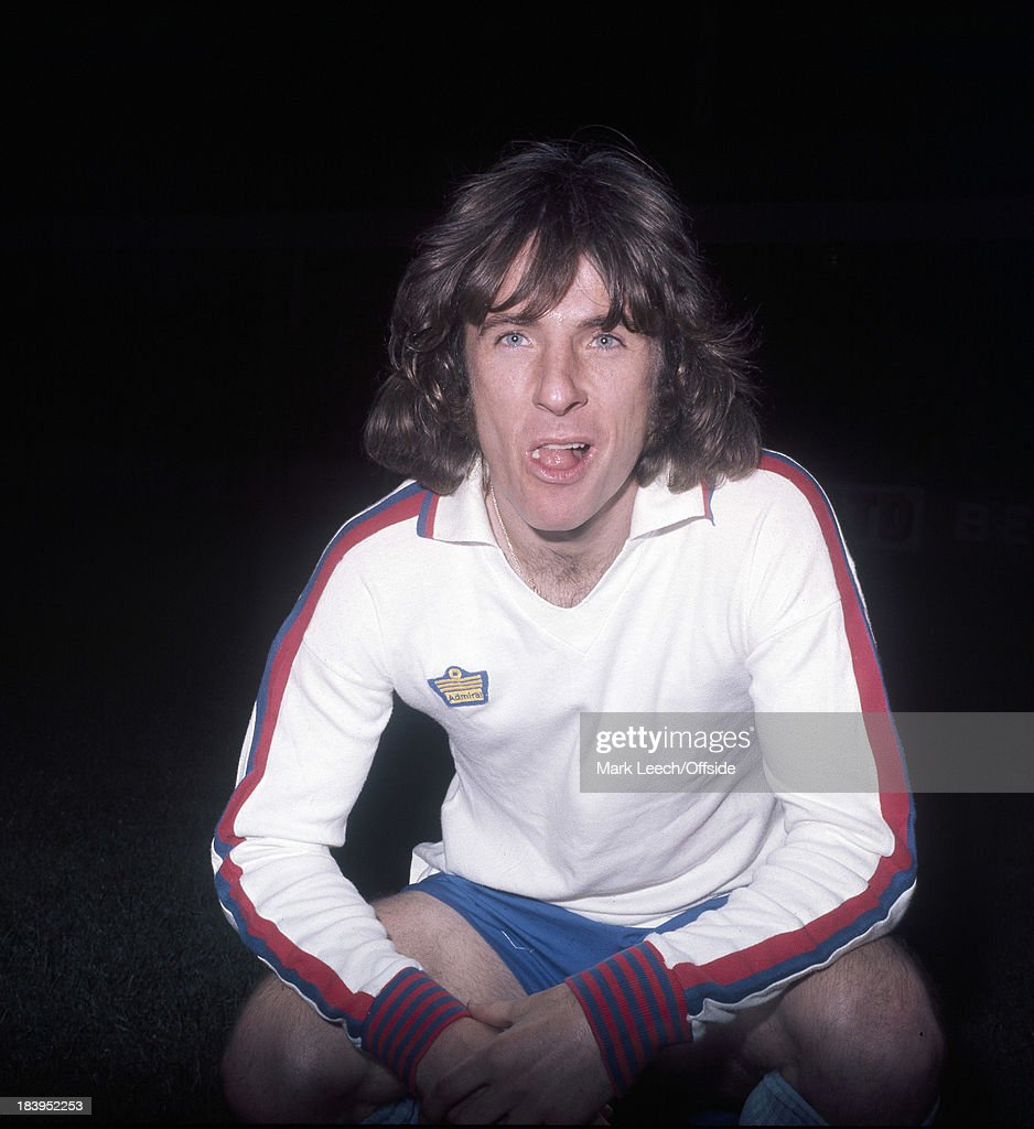 Stan Bowles poses in a replica England football shirt.
