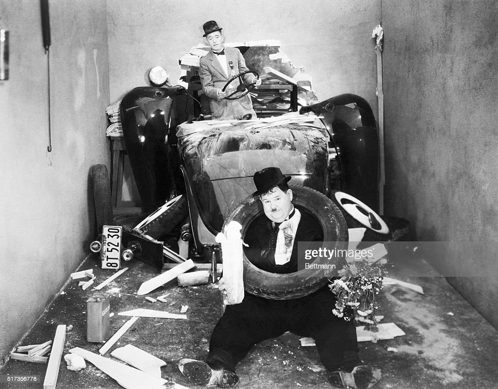 Stan Laurel and Oliver Hardy crashing through the wall in their automobile. Still from a 1938 movie.