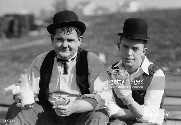 Stan Laurel and Oliver Hardy stop for milk and sandwiches during a break from filming the silent short 'The Finishing Touch' directed by Leo McCarey...
