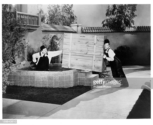 Stan Laurel and Oliver Hardy will a wooden crate between them in a scene from the film 'The Music Box' 1932