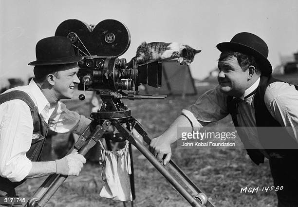 Stan Laurel and Oliver Hardy with a kitten during filming of the silent short 'The Finishing Touch' directed by Leo McCarey and Clyde Bruckman