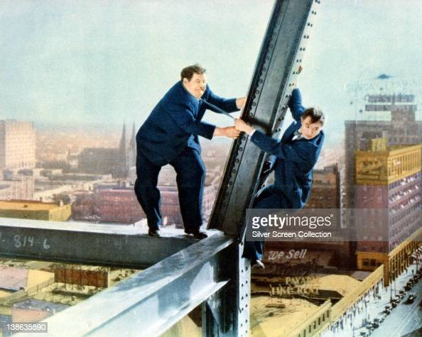 Stan Laurel British comedian and Oliver Hardy US comedian with Laurel hanging onto Hardy's tie as the stand on a skyscraper under construction in a...