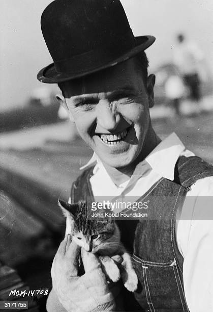 Stan Laurel holds a kitten during filming of 'The Finishing Touch' directed by Leo McCarey and Clyde Bruckman