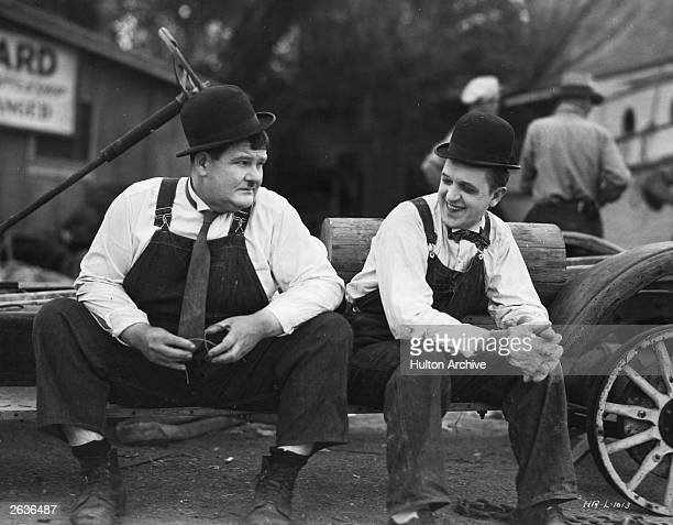 Stan Laurel the stage name of Arthur Stanley Jefferson the British born comedian and Oliver Hardy the portly American comedian are resting in between...