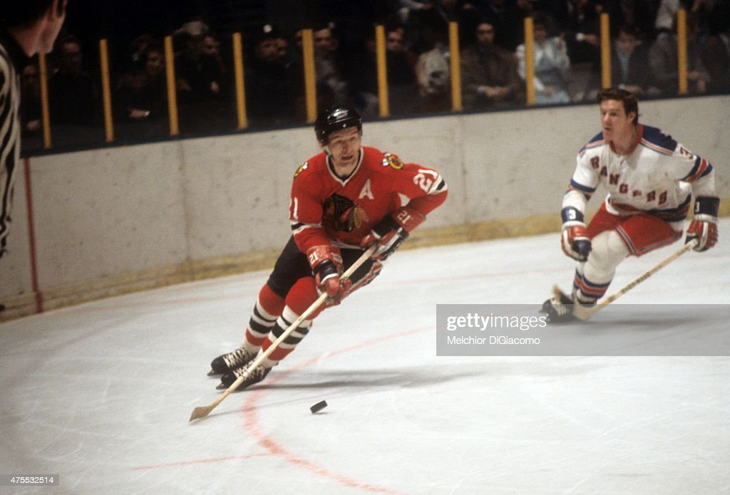 <a gi-track='captionPersonalityLinkClicked' href=/galleries/search?phrase=Stan+Mikita&family=editorial&specificpeople=1691052 ng-click='$event.stopPropagation()'>Stan Mikita</a> #21 of the Chicago Blackhawks skates with the puck as Ron Harris #3 of the New York Rangers defends circa 1973 at the Madison Square Garden in New York, New York.