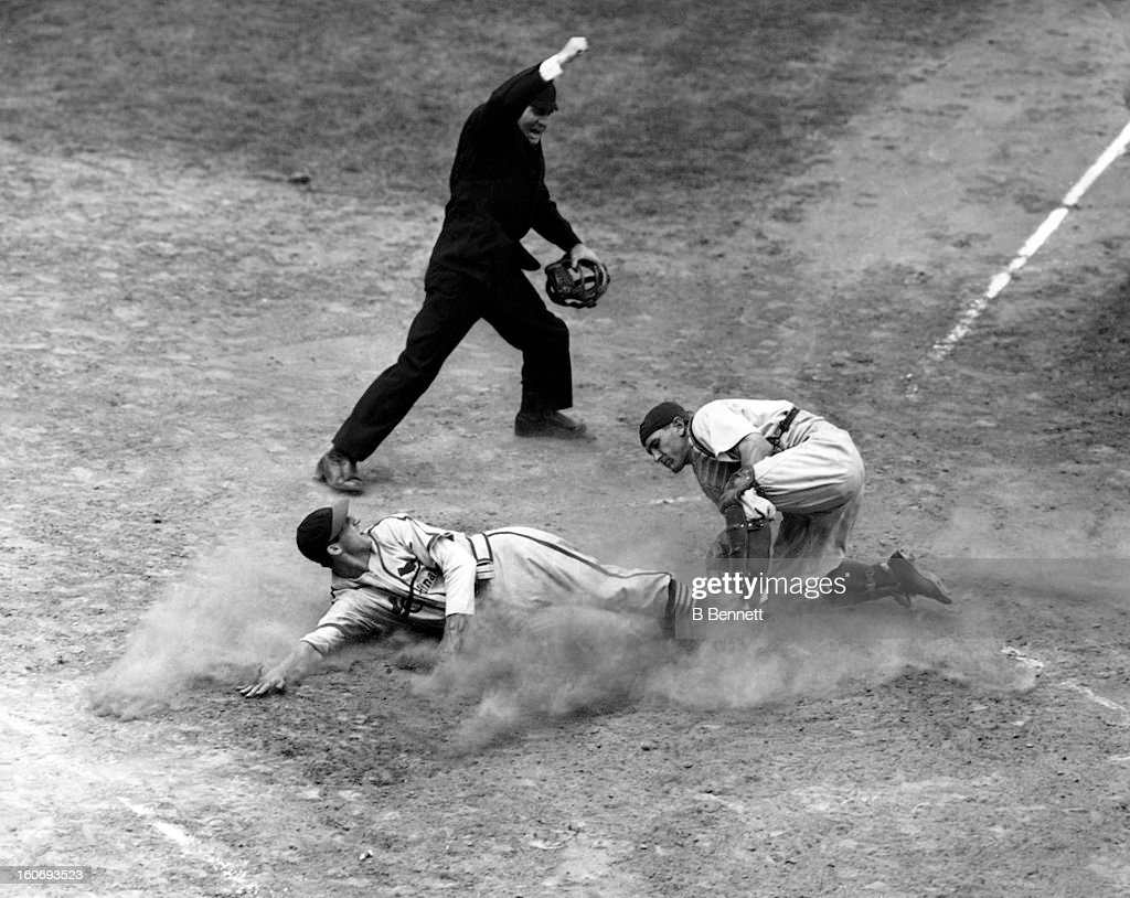 Stan Musial of the St. Louis Cardinals is tagged out at home by catcher Bruce Edwards of the Brooklyn Dodgers as home plate umpire Babe Pinelli makes the call on September 13, 1946 at Ebbets Field in Brooklyn, New York.